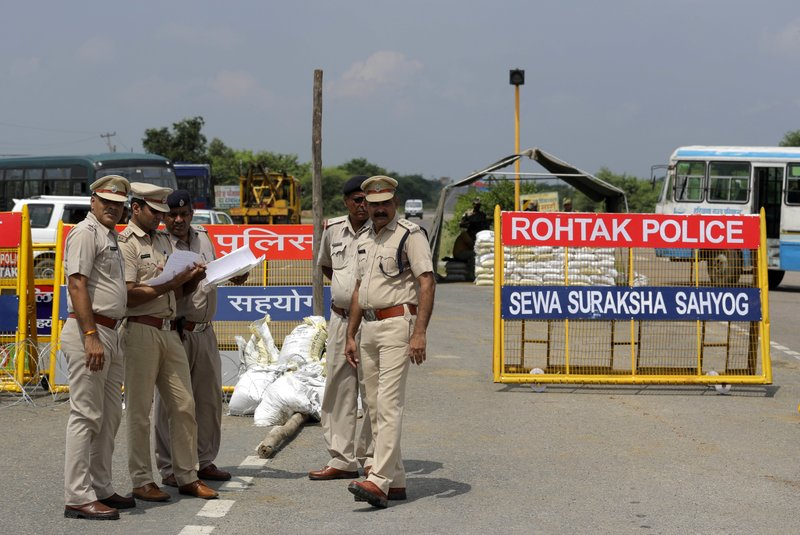 Indian policemen stand guard at a temporary road blockade near Sunaria Jail where Dera Sacha Sauda sect chief Gurmeet Ram Rahim Singh is lodged in Rohtak, some 80 kilometres (50 miles) from New Delhi, India, Monday, Aug. 28, 2017. A curfew is in place in a north Indian town where a spiritual guru who was convicted of rape last week is scheduled to be sentenced on Monday. A judge will travel to the prison where the bling-loving guru has been held since being convicted Friday. The conviction sparked deadly protests.