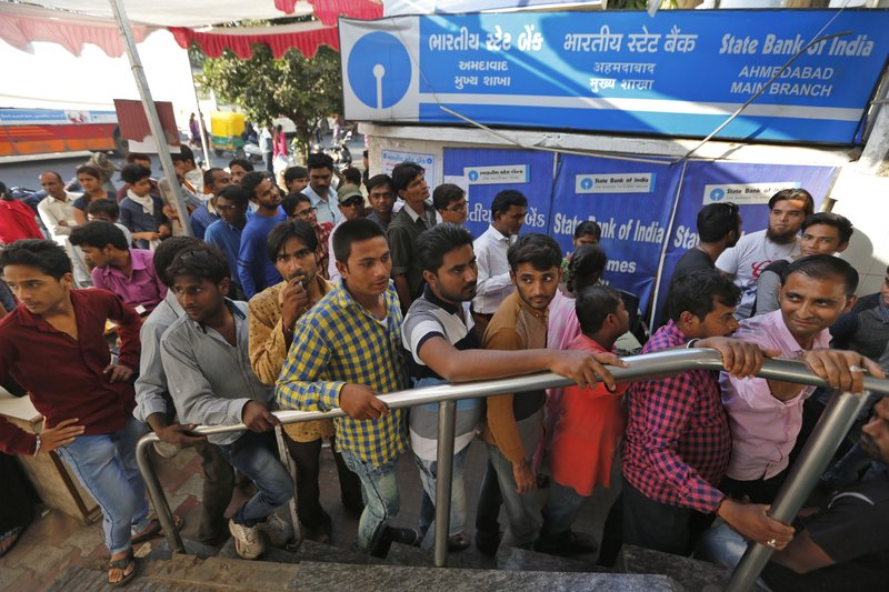 In this Nov. 20, 2016, file photo, Indians stand in a queue to withdraw and deposit currency at an ATM a week after India announced that it was withdrawing 500 and 1,000 rupee notes as legal tender to fight corruption and tax evasion, in Ahmadabad, India. Prime Minister Narendra Modi came to power on a euphoric wave of promises to boost the economy. Three years later, India's economic prospects are looking decidedly more grim. India's economic expansion has slowed to its lowest level in three years. Small businesses are struggling, or even shutting down, after a major overhaul of both the country's currency and its sales tax system.