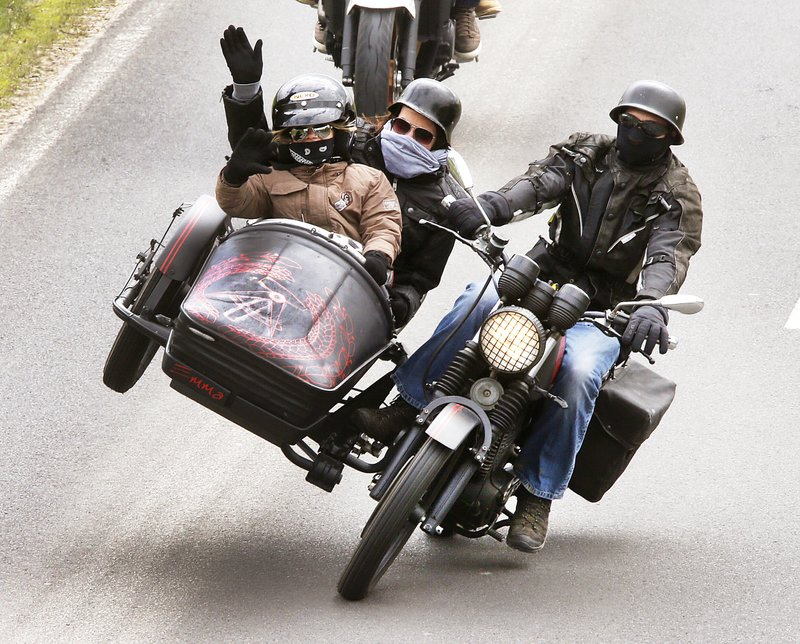 A biker with family members in the side car takes part in a convoy of about thousands of others in Diebach am Haag, Germany, on Sunday, April 23, 2017. The convoy followed a Mass marking the opening of the biker season.