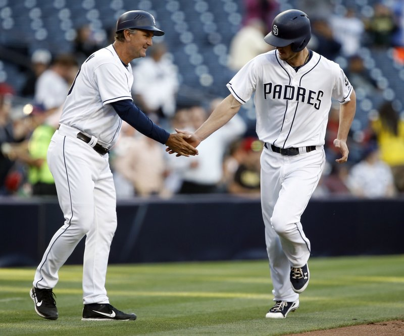 San Diego Padres third base coach Glenn Hoffman, left, congratulates Wil Myers for hitting a solo home run against the Arizona Diamondbacks during the first inning of a baseball game in San Diego, Thursday, April 20, 2017. (AP Photo/Alex Gallardo)