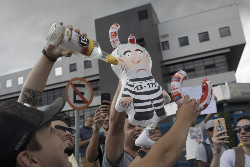 c407fed46079e A demonstrator against Brazil's former President Luiz Inacio Lula da Silva  holds a doll dressed as an inmate featuring the face of da Silva, ...