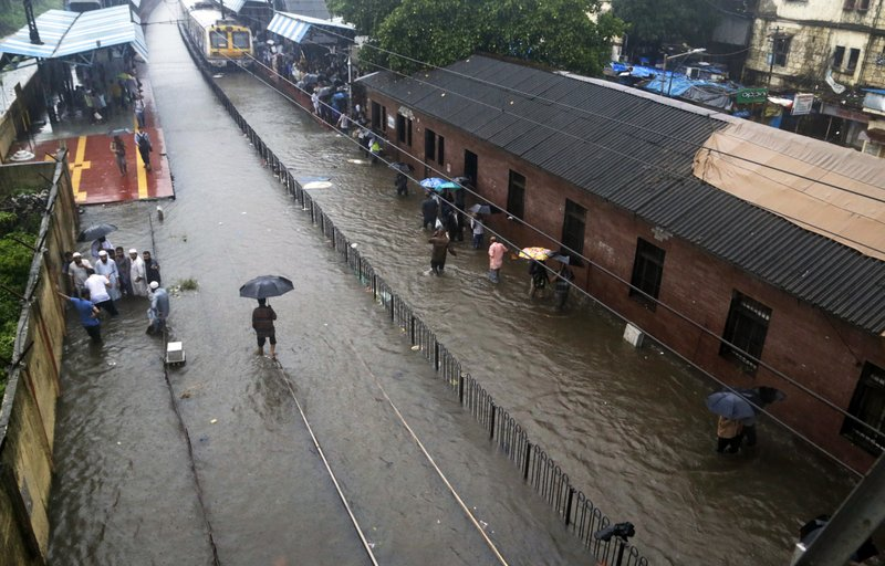 In this Tuesday, Aug. 29, 2017 file photo, people walk past a waterlogged railway station during heavy rainfall in Mumbai, India. Two massive, rain-soaked cities on opposite sides of the world are struggling with swirling, brackish waters that have brought death and devastation. For Houston, it's unprecedented. For Mumbai, it's painfully common. India's financial capital was especially hard hit, with water swamping offices, schools and roads and about 60 people killed, 33 alone in Thursday's collapse of a 117-year-old apartment building whose foundation had been weakened by the flooding.