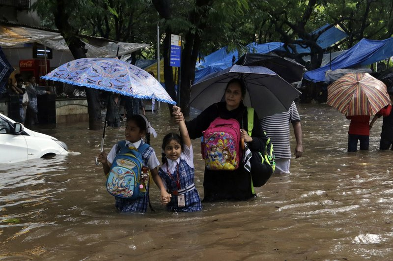 School children wade through a waterlogged street following heavy rains in Mumbai, India, Tuesday, Aug. 29, 2017. Heavy rains Tuesday brought Mumbai to a halt flooding vast areas of the city.