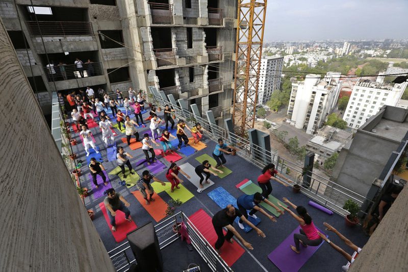 Indians performs yoga on a walk-way between two towers of an under construction high rise residential building as they mark International Yoga Day in Ahmadabad, India, Thursday, June 21, 2018. Yoga enthusiasts across the world Thursday took part in mass yoga events to mark International Yoga Day.