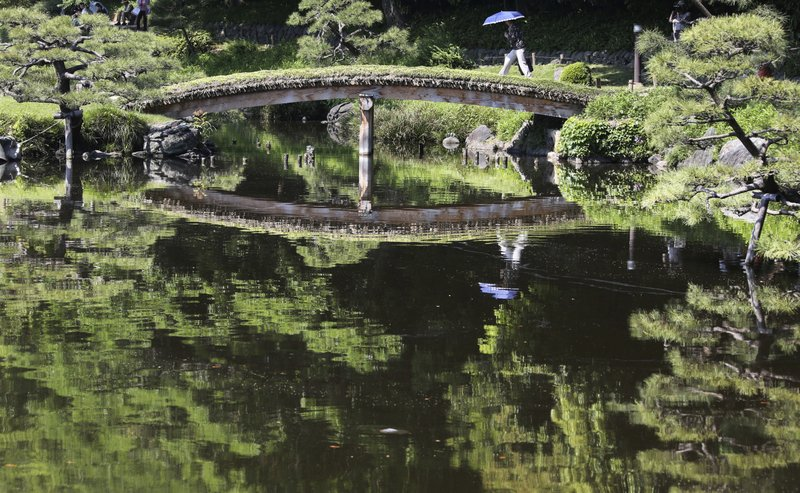 In this Friday, May 19, 2017, photo, a woman carrying an umbrella crosses a bridge on a pond at Kiyosumi Gardens in Tokyo. The temperature in Tokyo soared to 26.3 degrees Celsius (79 degrees Fahrenheit).
