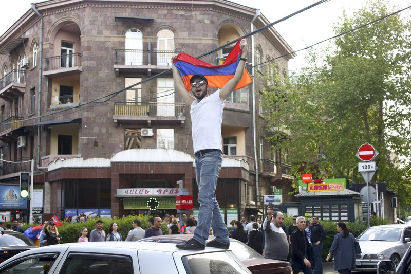 A man waves an Armenian national flag celebrating Armenian Prime Minister's Serzh Sargsyan's resignation in Republic Square in Yerevan, Armenia, Monday, April 23, 2018.