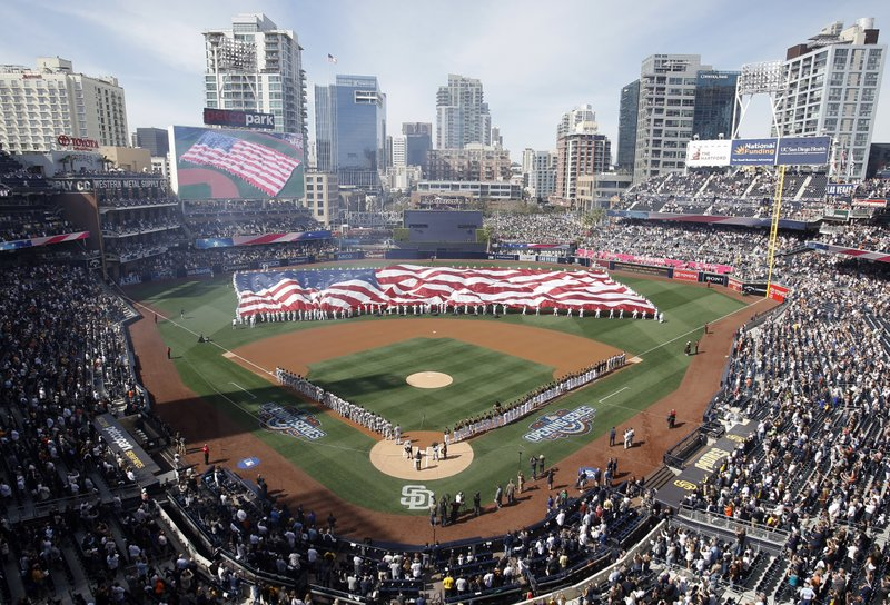 A giant U.S. flag is displayed during opening ceremonies for a baseball game between the San Diego Padres and the San Francisco Giants in San Diego, Friday, April 7, 2017. (AP Photo/Alex Gallardo)