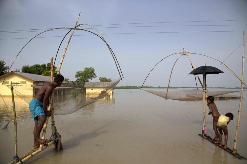 In this Tuesday, Aug. 15, 2017, file photo, villagers fish in floodwaters in Morigaon district, east of Gauhati, northeastern state of Assam. This week's flooding in Houston is unprecedented, but such devastation is chronic across South Asia. Experts say local officials are ignoring dangers and pursuing development plans that only increase the risk of flood-related death and destruction as annual monsoon rains challenge cities to cope.