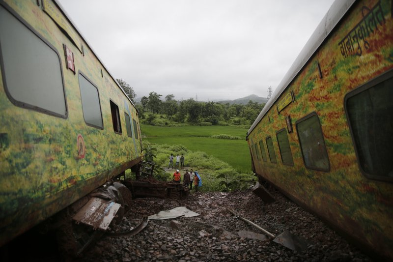 People look at derailed coaches of the Duronto Express in Asangaon, some 70 kilometers from Mumbai, India, Tuesday, Aug. 29, 2017. A passenger train partly derailed Tuesday morning in western India, the third rail accident in the country in 10 days. Rescuers were working to pull out people who were trapped in the toppled train engine and seven coaches lying on their sides. No casualties or injuries have been reported, railway spokesman A.K. Jain said.