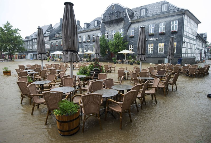 Tables and chairs of a cafe sit empty in the flooded Marktplatz square in Goslar, Germany, Wednesday, July 26, 2017. Heavy rains in Germany have led to flooding in some areas.