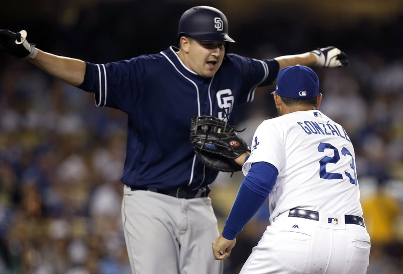 Los Angeles Dodgers' first baseman Adrian Gonzalez, right, tags out San Diego Padres' Trevor Cahill on a sacrifice bunt during the fifth inning of a baseball game in Los Angeles, Wednesday, April 5, 2017. (AP Photo/Alex Gallardo)