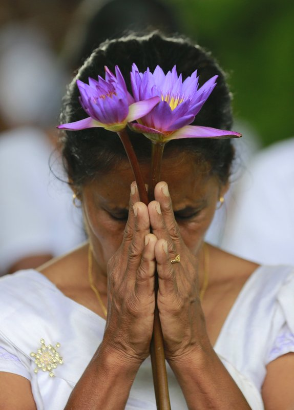In this Friday, May 19, 2017 photo, a family member of fallen Sri Lankan government soldier pays homage at the national war heroes memorial in Colombo, Sri Lanka. Sri Lanka marked the eighth anniversary of the end of its bloody civil war on Friday with much of the legacy and divisions created by more than quarter-century of violence still intact.