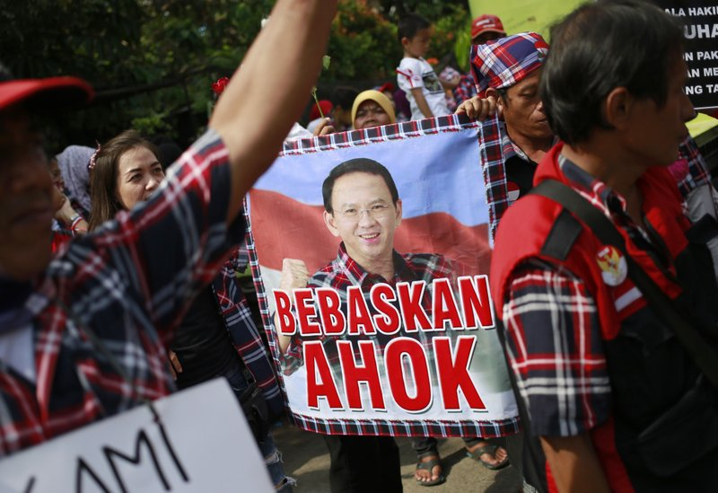 "Supporters of Jakarta Governor Basuki ""Ahok"" Tjahaja Purnama display a poster that reads ""Free Ahok"" during a rally outside the court where his sentencing hearing is held in Jakarta, Indonesia, Tuesday, May 9, 2017. The minority Christian governor is currently on trial on accusation of blasphemy following his remark about a passage in the Quran that could be interpreted as prohibiting Muslims from accepting non-Muslims as leaders."