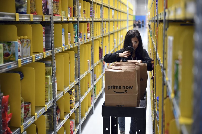 In this Thursday, July 27, 2017, file a staff member collects merchandise for customers' orders from shelves at the newly-opened Amazon Prime Now facility in Singapore. Amazon introduced express delivery in Singapore in its first direct effort to win over Southeast Asian digital natives and new internet users. The American e-commerce company announced Thursday it will begin operating a 100,000 square foot (9,290 square meter) distribution facility in the wealthy island nation.