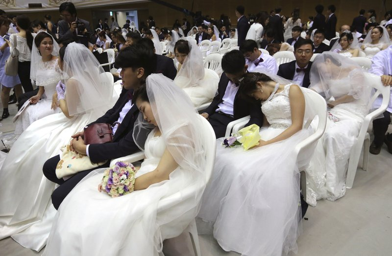 In this Thursday, Sept. 7, 2017, file photo, brides takes a nap before a mass wedding ceremony at the Cheong Shim Peace World Center in Gapyeong, South Korea. About 4,000 South Korean and foreign couples exchanged or reaffirmed marriage vows in the Unification Church's mass wedding arranged by Hak Ja Han Moon, wife of the late Rev. Sun Myung Moon, the controversial founder of the Unification Church.