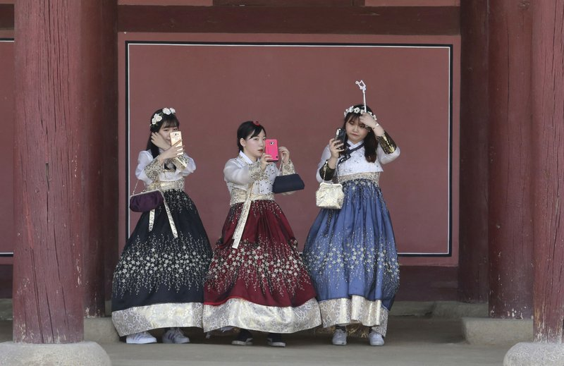 "In this Thursday, May 18, 2017 photo, women dressed in South Korean traditional ""Hanbok"" attire adjust their hair to take pictures at the Gyeongbok Palace, the main royal palace during the Joseon Dynasty, in Seoul, South Korea. Wearing a ""Hanbok,"" mostly rented, has become a fashionable trend among the youth commonly seen at palaces and other traditional places."
