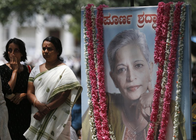 "Mourners stand next to a portrait of Indian journalist Gauri Lankesh during the public viewing of her body in Bangalore, India, Wednesday, Sept. 6, 2017. The Indian journalist was gunned down outside her home the southern city of Bangalore — the latest in a string of deadly attacks targeting journalists or outspoken critics of religious superstition and extreme Hindu politics. Kannada reads, ""Heartfelt Condolences""."