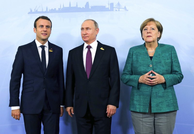 German Chancellor Angela Merkel, right, poses with French President Emmanuel Macron, left, and Russia's President Vladimir Putin prior to a meeting during the G20 summit in Hamburg, Germany, Saturday, July 8, 2017. Leaders of the world's top economic powers are wrapping up their search for common ground on trade, climate change and a host of other issues at the Group of 20 summit in Hamburg Saturday, a meeting overshadowed by violent clashes between anti-globalization activists and police.