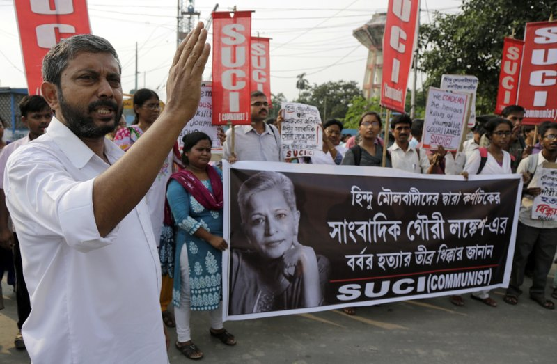 Activists of Socialist Unity Center of India- Communist (SUCI-C) march with a banner showing a portrait of Indian journalist Gauri Lankesh at a protest demonstration against her killing in Kolkata, India, Wednesday, Sept. 6, 2017. The killing of the Indian journalist has provoked outrage and anguish across the country, with thousands protesting what they see as part of an ongoing campaign to silence critics of India's ruling Hindu nationalist party.