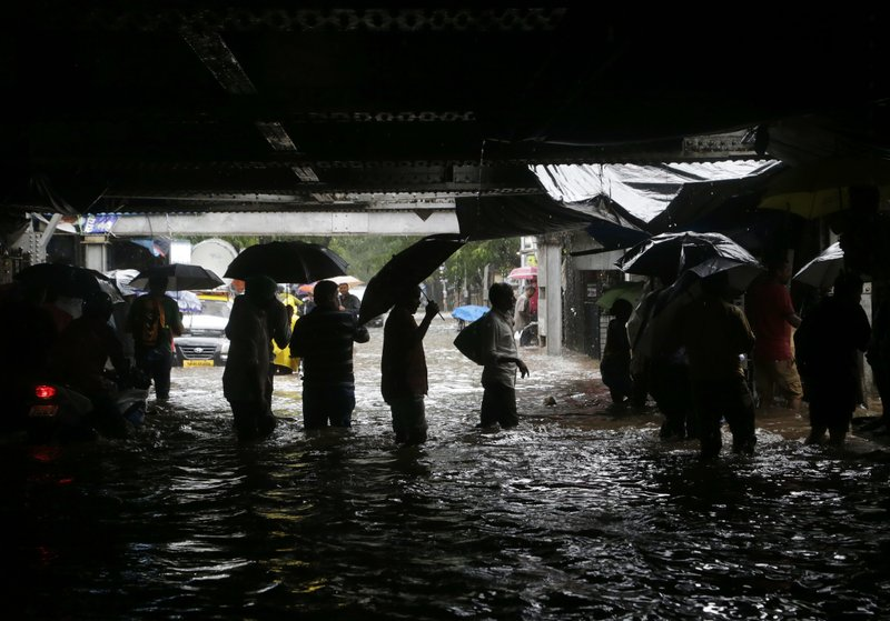People walk through a waterlogged street following heavy rains in Mumbai, India, Tuesday, Aug. 29, 2017. Heavy rains Tuesday brought Mumbai to a halt flooding vast areas of the city.