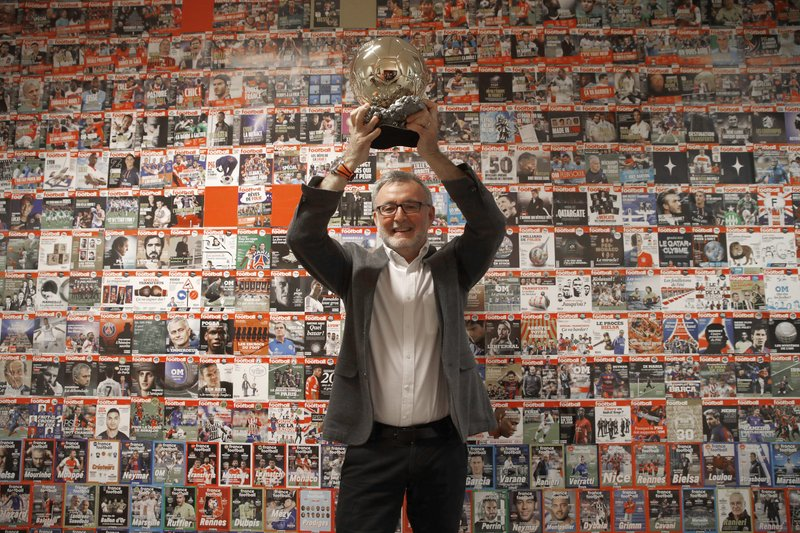 France Football magazine chief editor Pascal Ferre poses with the Golden Ball during a interview with The Associated Press
