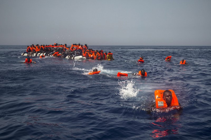 African migrants try to reach a Spanish NGO Proactiva Open Arms rescue ship after falling from a punctured rubber boat in the Mediterranean Sea, about 12 miles north of Sabratha, Libya on Sunday, July 23, 2017. Hundreds of thousands of migrants are smuggled out of Libya across the Mediterranean Sea to Europe each year by traffickers using unseaworthy craft.
