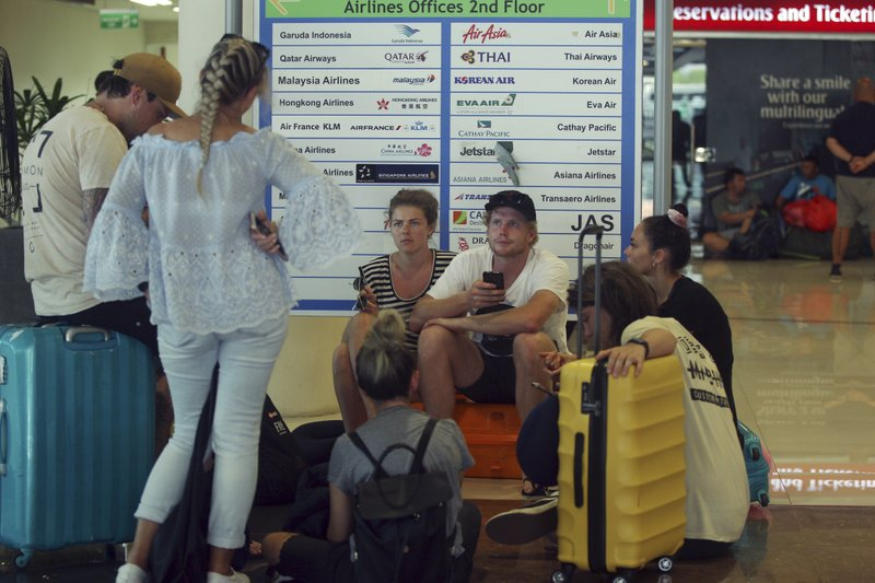 Tourists wait as Ngurah Rai International Airport is closed due to the eruption of Mount Agung in Bali, Indonesia Friday, June 29, 2018. The Indonesian tourist island of Bali closed its international airport Friday, stranding thousands of travelers, as the Mount Agung volcano gushed a 2,500-meter (8,200-feet) column of ash and smoke.