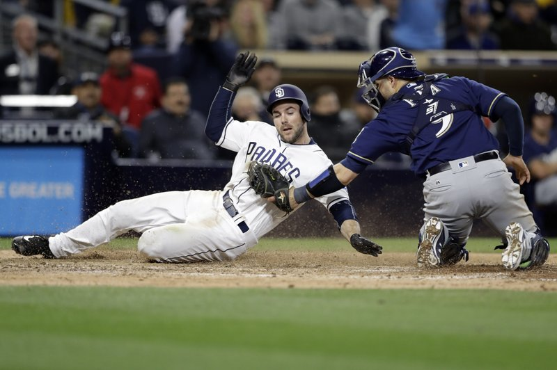 Milwaukee Brewers catcher Manny Pina tags out San Diego Padres' Matt Szczur during the seventh inning of a baseball game Tuesday, May 16, 2017, in San Diego. (AP Photo/Gregory Bull)