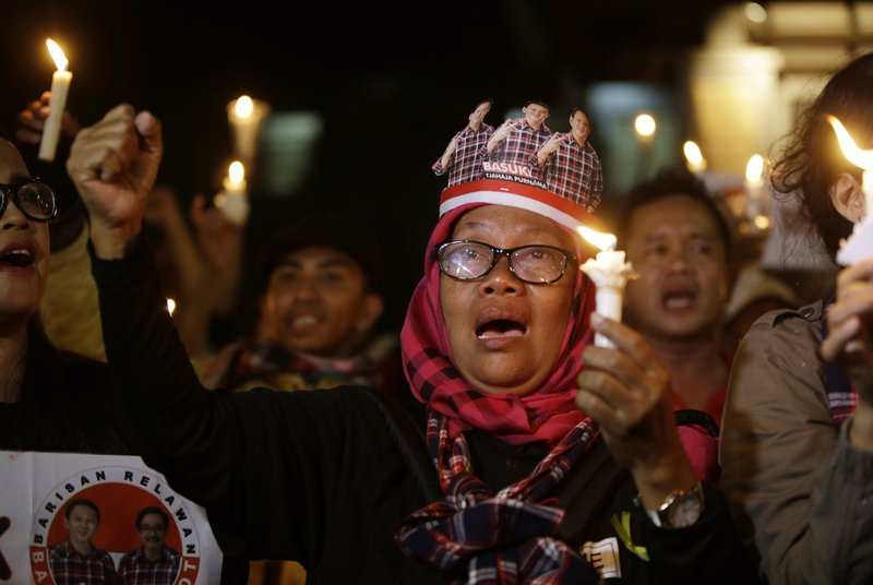 "In this Tuesday, May 16, 2017, photo, supporters of Jakarta Gov. Basuki ""Ahok"" Tjahaja Purnama who was imprisoned for blaspheming Islam, hold candles during a protest outside the High Court in Jakarta, Indonesia. The imprisonment of Ahok, a Christian politician, has triggered an outpouring of anger and support around Indonesia."