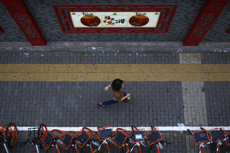 "In this Tuesday, Sept, 26, 2017, file photo, a woman walks by bicycles from a bike-sharing company parked along a wall displaying a government propaganda poster promoting the ""China Dream"" in Beijing. The Asian Development Bank raised its growth forecast Tuesday for Asia's developing economies because global trade and conditions in the world's biggest economies are improving more than expected."