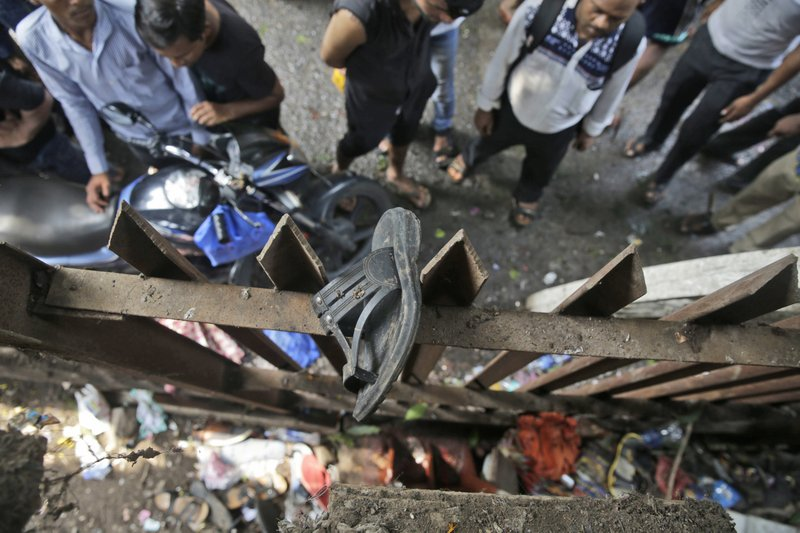 A slipper of an injured commuter is seen stuck on the railing of a pedestrian bridge where a stampede took place at the Elphinstone station, in Mumbai, India, Friday, Sept. 29, 2017. The stampede broke out on a crowded pedestrian bridge connecting two railway stations in Mumbai during the Friday morning rush, killing a number of people police said.