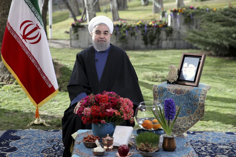 In this photo released by official website of the Iranian Presidency on Monday, March 20, 2017, behind the New Year's table items President Hassan Rouhani poses for a portrait in a session to deliver a message for the Iranian New Year, Iran. Nowruz, a festival to celebrate the new Persian year starts with the spring. Iranians follow the Persian solar year, and this year, they begin the year 1396.