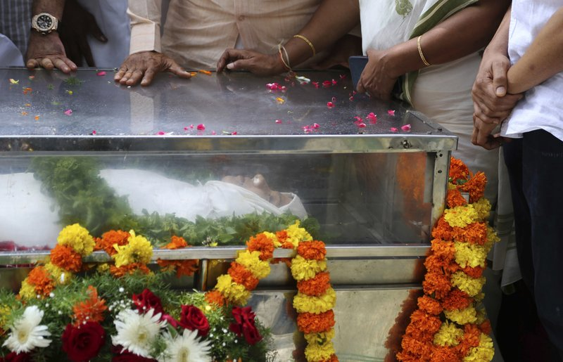 Mourners stand next to the casket of Indian journalist Gauri Lankesh placed for public viewing in Bangalore, India, Wednesday, Sept. 6, 2017. The Indian journalist was gunned down outside her home the southern city of Bangalore — the latest in a string of deadly attacks targeting journalists or outspoken critics of religious superstition and extreme Hindu politics.