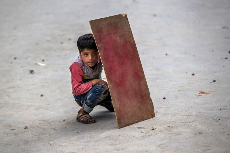 In this Friday. May 19, 2017, photo, a Kashmiri boy shields himself from stones and glass marbles with plywood during a clash between Indian policemen and protesters in Srinagar, Indian-controlled Kashmir. Government forces fired tear gas during clashes with Kashmiri protesters in the Indian-controlled portion of Kashmir after Friday prayers called by separatist leaders against the continuous detention of woman separatist leader Asiya Adrabi, chairman of Dukhtaran-e-Millat, or Daughters of the Nation. They also demanded the release of all political prisoners from Indian prisons.