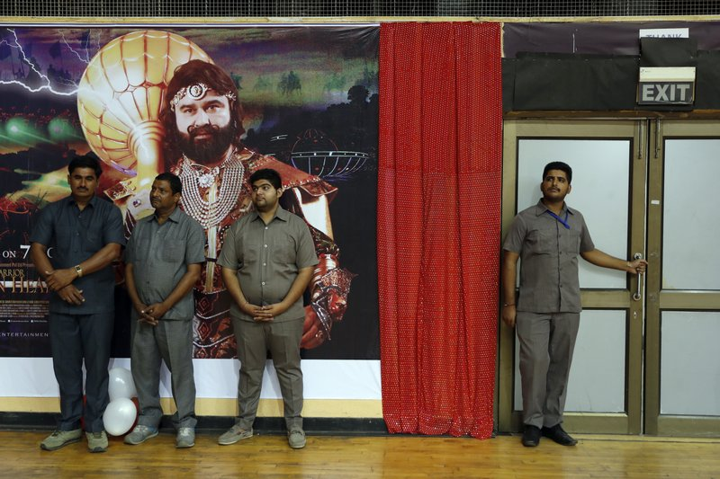 "In this Oct. 5, 2016, file photo, security officers stand watch by a poster of Indian spiritual guru, who calls himself Dr. Saint Gurmeet Singh Ram Rahim Insan, during a press conference ahead of the release of the guru's film ""MSG, The Warrior Lion Heart,"" in New Delhi, India. A judge on Monday, Aug. 28, 2017, sentenced the popular and flamboyant Indian spiritual guru to prison on charges of raping two female followers."