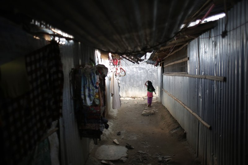 In this Sunday, Sept. 10, 2017, photo, a young Rohingya girl walks inside a temporary shelter at a camp in Kathmandu, Nepal. Recent violence in Myanmar has driven hundreds of thousands of Rohingya Muslims to seek refuge across the border in Bangladesh. Only about 250 Rohingya live in Nepal since anti-Muslim riots erupted in Myanmar in 2012, according to the U.N. refugee agency, which offers them education and medical support. The refugees live in a ramshackle camp carved out on a slope on the outskirts of the capital, Kathmandu. Their huts of tin, bamboo and plastic sheets are connected by narrow stone steps.