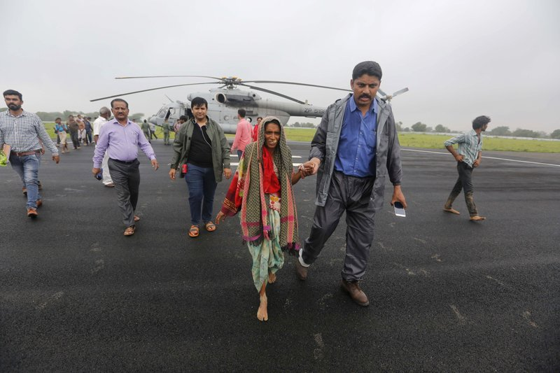 An Indian man escorts a woman who was air lifted from a flooded farm after she arrived at an airport in Deesa, Gujarat, India, Wednesday, July 26, 2017. At least 29 people have died in the state of Gujarat amid torrential rains. This week's deaths have taken the toll the state to 83 since the start of the monsoon season which runs from June through September.