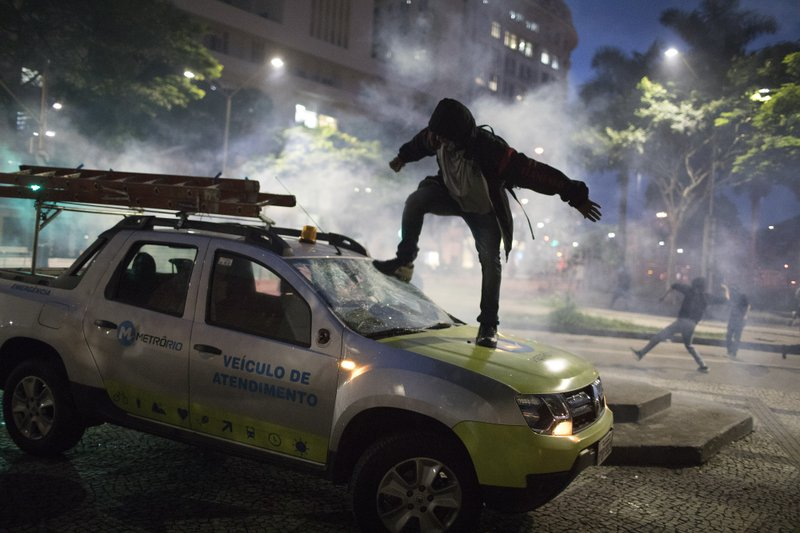 A demonstrator breaks the windshield of a truck that belongs to a subway maintenance crew after clashes with police broke out during a general strike in Rio de Janeiro, Brazil, Friday, April 28, 2017. Public transport largely came to a halt across much of Brazil on Friday and protesters blocked roads and scuffled with police as part of a general strike to protest proposed changes to labor laws and the pension system.