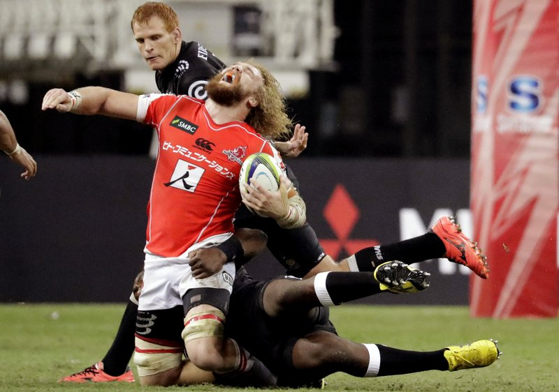 In this Saturday, May 20, 2017 photo, Willem Britz of Japan's Sunwolves gets tackled by Tendai Mtawarira of South Africa's Sharks during their Super Rugby match in Singapore.
