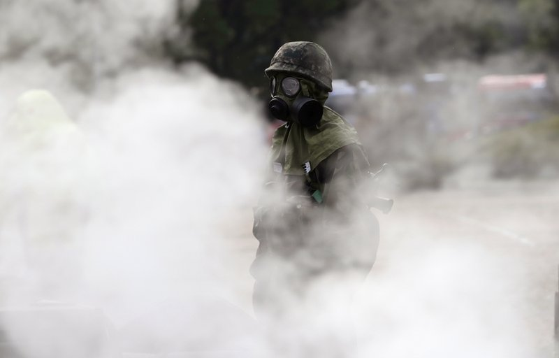 In this Wednesday, Sept. 27, 2017, file photo, a South Korean military soldier wearing anti-chemical gears participates in smoke during a drill against chemical bomb attack as a part of Hwarang Exercise in Seoul, South Korea. About 300 people from various related organizations including civil, government, fire station, military and police participated in the drill to protect South Korea's capital Seoul.