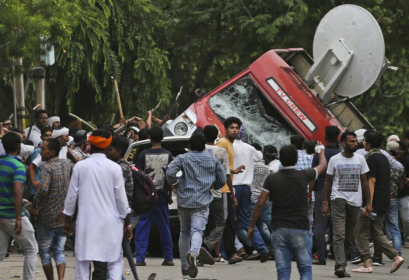 Dera Sacha Sauda sect members overturn an OB van on the streets of Panchkula, India, Friday, Aug. 25, 2017. Deadly riots have broken out in a north Indian town after a court convicted their guru, who calls himself Saint Dr. Gurmeet Ram Rahim Singh Ji Insaan, of raping two of his followers. Mobs also attacked journalists and set fire to government buildings and railway stations.