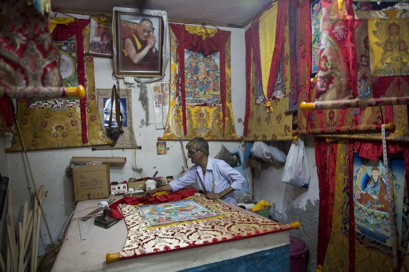 An Indian man prepares a thangka to hang on wall at a Tibetan colony in New Delhi, India, Tuesday, April 4, 2017. India said Tuesday that China should not interfere in its internal affairs, as the Dalai Lama began a weeklong visit to India's remote northeast that Beijing has protested.