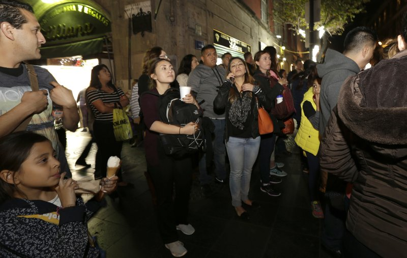 In this Dec. 22, 2016 photo, Mexican youth who migrated to the U.S. as children walk through downtown Mexico City, on their first night back in their native country. More than 100 former child migrants have visited the country of their birth on five such trips sponsored by California State University, Long Beach, emotional journeys to what is often a barely remembered homeland, to reunite with family seen only in photos or on Skype. (AP Photo/Marco Ugarte)