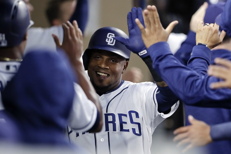 San Diego Padres' Erick Aybar is greeted by teammates after scoring on a two-RBI double by Hunter Renfroe during the second inning of a baseball game against the Milwaukee Brewers, Monday, May 15, 2017, in San Diego. (AP Photo/Gregory Bull)