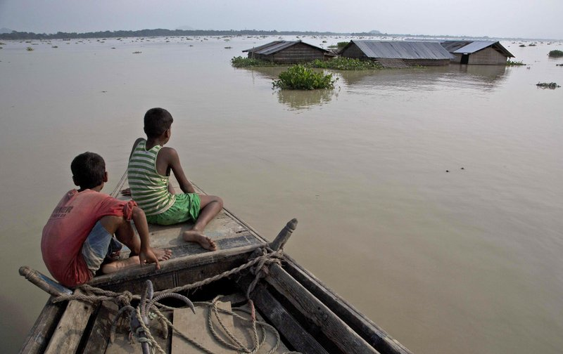 In this Aug. 15, 2017, file photo, flood affected villagers travel by boat in floodwaters in Morigaon district, east of Gauhati, northeastern state of Assam. This week's flooding in Houston is unprecedented, but such devastation is chronic across South Asia. Experts say local officials are ignoring dangers and pursuing development plans that only increase the risk of flood-related death and destruction as annual monsoon rains challenge cities to cope.