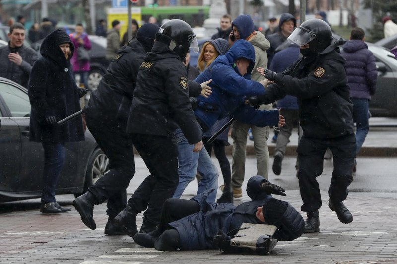 A woman, pushed to the ground by Belarus police tries to defends herself as the police detain an activist during an opposition rally in Minsk, Belarus, Saturday, March 25, 2017. A cordon of club-wielding police blocked the demonstrators' movement along Minsk's main avenue near the Academy of Science. Hulking police detention trucks were deployed in the city center.
