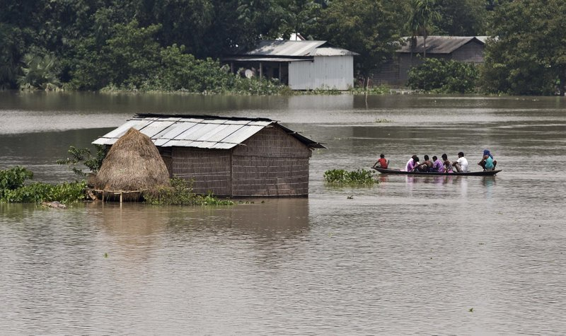 Flood affected people travel in a boat near partially submerged houses in Morigaon district east of Gauhati, Assam, India, Tuesday, Aug. 15, 2017. Heavy monsoon rains have unleashed landslides and floods that killed dozens of people in recent days and displaced millions more across northern India, southern Nepal and Bangladesh.