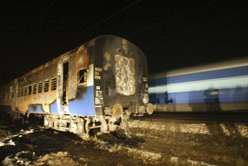 In this Feb.22, 2007, file photo, Pakistan bound Samjhauta Express, moves past the damaged coaches of Sunday's fire in Deewana, about 80 kilometers (50 miles) north of New Delhi, India. 68 people were killed by bombs and an ensuing fire aboard the Samjhauta Express, a train link between India and Pakistan set up under a three-year peace process between the South Asian arch rivals.