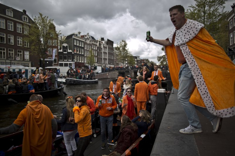 People dance on a boat during King's Day celebrations in Amsterdam, Netherlands, Thursday, April 27, 2017. The Netherlands is marking the 50th birthday of King Willem-Alexander with orange-clad citizens holding parties and street sales throughout the country.