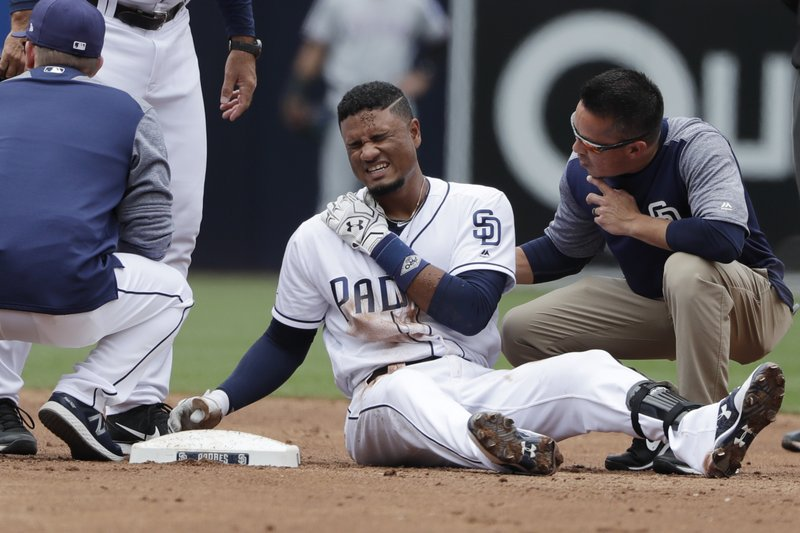 San Diego Padres' Allen Cordoba reacts after injuring himself sliding in late to second base during the third inning of a baseball game against the Texas Rangers, Tuesday, May 9, 2017, in San Diego. (AP Photo/Gregory Bull)